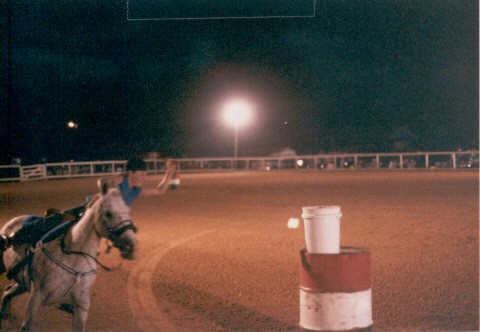 Young girl riding a horse at the rodeo